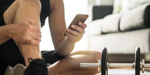 Mann mit Smartphone zur Darstellung des Online Fitness-Coachings